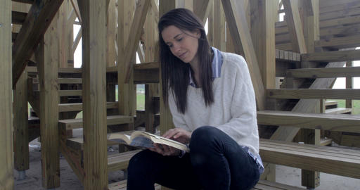 Beautiful woman reading outdoors on stairs – 4K Footage