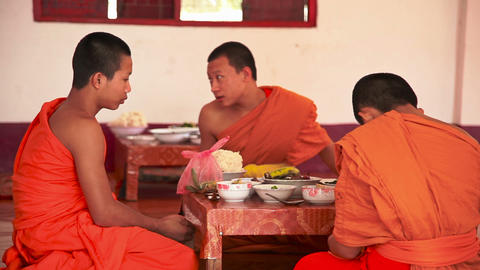 Monks have lunch at the table in monastery. Luang Prabang city, Laos Live Action