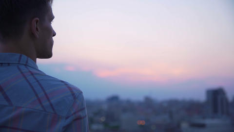 Guy peering into pink horizon of city landscape, thinking about life, freedom Footage