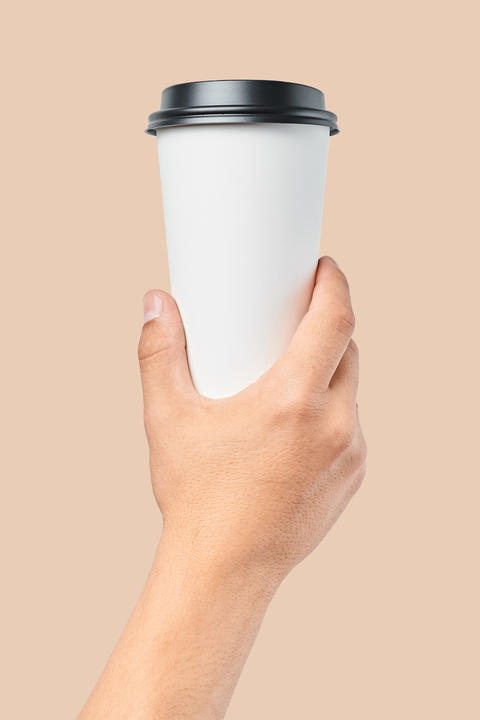 Mockup of men's hand holding white paper large size cup with black cover Photo