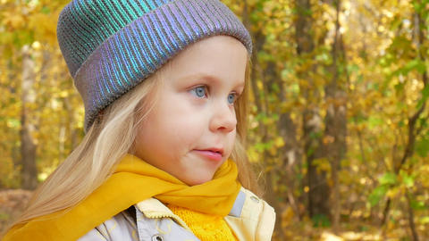 Little cute girl in blue neon color hat and yellow scarf is smiling at park in Footage