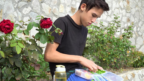 Teenager eating a homemade healthy food outdoors Live Action
