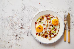 Two fresh fried eggs with crunchy crisp bacon and chive served on rustic plate Fotografía
