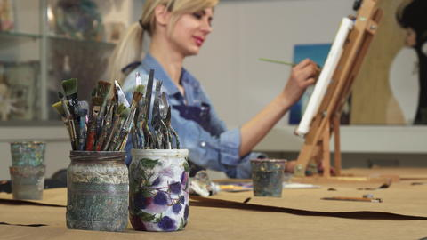 Selective focus on a bunch of paintbrushes female artist working on her painting Photo
