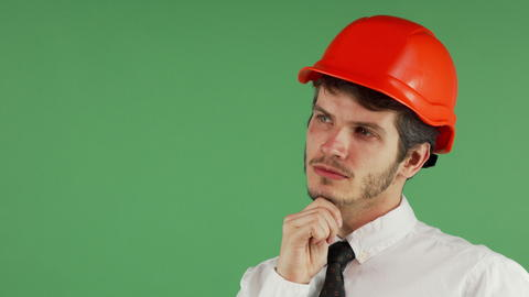 Handsome male constructionist in a hardhat looking away thoughtfully フォト