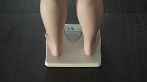 Female measuring weight, stepping on scales, questioning herself if go on diet Live Action