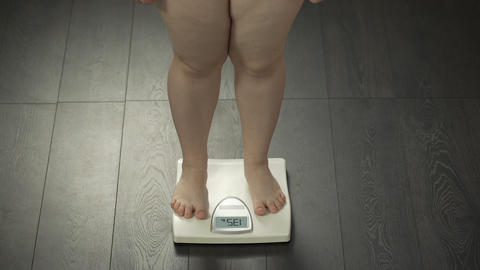 Legs of woman stepping on home scales, normal weight, successful diet result Live Action