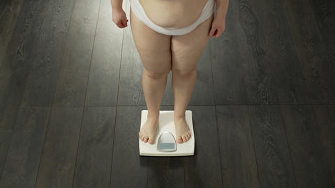Woman stepping on bathroom scales to measure weight, unsuccessful diet, failure Live Action
