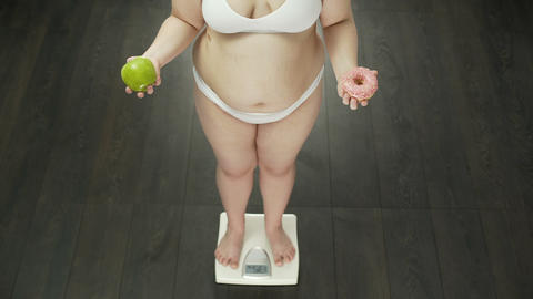 Chubby woman standing on scales with apple and donut, choosing sweets, nutrition Live Action