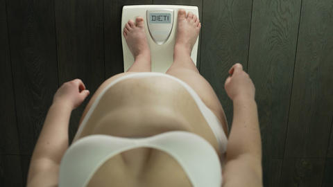 Overweight female standing on scales with word diet on screen, serious problems Live Action