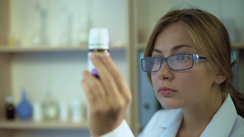 Female doctor studying medicine ingredients, staring at label of pill container Footage