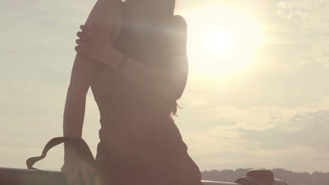 Girl leaning on handrail in street against sunlit sky, touching arm as if cold Footage