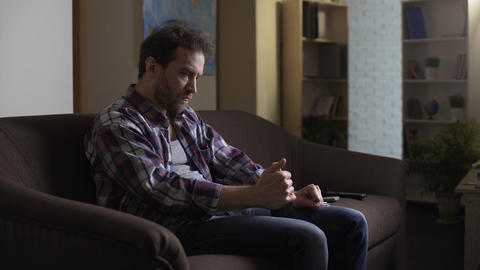 Man sitting on couch in dark room, trying to open beer bottle with fork, despair Live Action