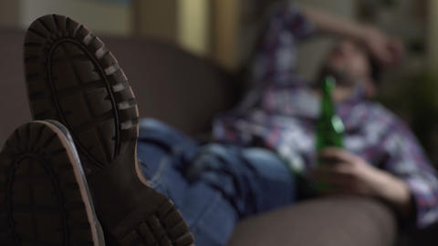 Drunk male sleeping on couch with bottle of beer in hand, bad news, emotions Live Action