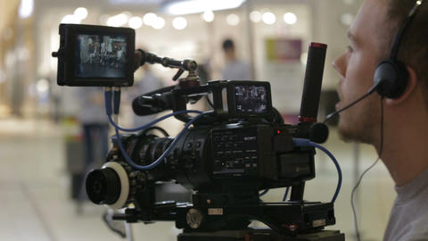 cameraman with headset shoots shopping mall gallery ビデオ