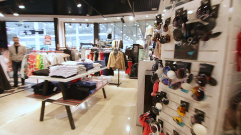 motion along fashion store with rich clothes selection Live Action