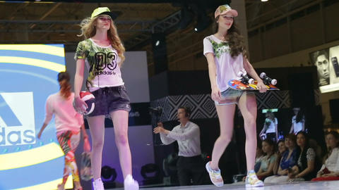 long haired ladies walk in modern sporty clothes on podium Live Action