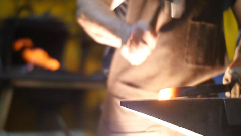 Blacksmith Forging Sword on an Anvil with Sparks in a Workshop in Slow Motion Footage