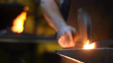 Blacksmith Banging Metal with his Hammer on an anvil Making Sparks Footage