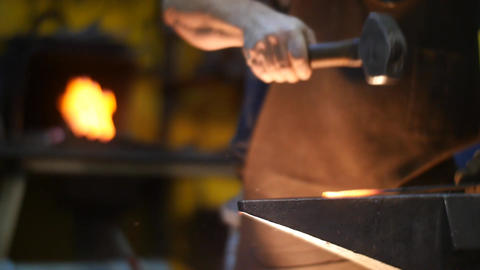 Blacksmith Hammering Hot Metal On An Anvil With Sparks In A Workshop Behind Him  stock footage