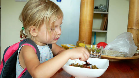 Side profile of little girl eating 영상물