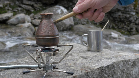 In the hike, coffee is prepared on a portable gas burner. Close-up. On the bank Footage