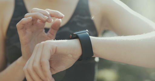 Woman using her smartwatch touchscreen wearable technology device in morning Live Action
