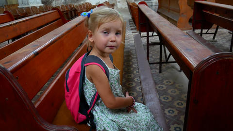 A little Catholic is sitting alone in an old empty church Footage