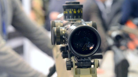 Weapon optics sight of sniper rifle with man close-up in store or shop Live Action