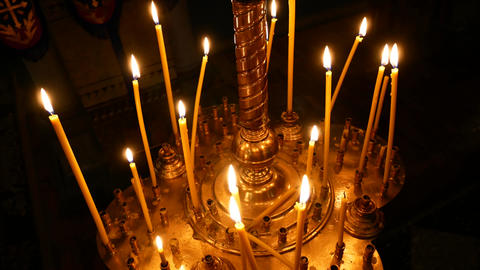 Burning candle closeup on the background of other candles in the Christian Footage