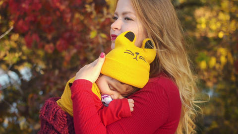 Mixed race family. Mother holds sleeping daughter in her arms in autumn park Footage