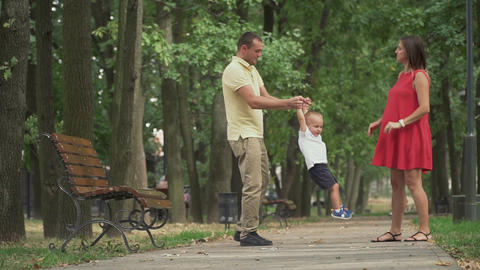 Dad holds hands and circles his little son in a circle Footage