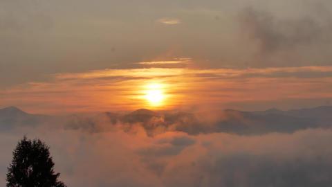 Brilliant summit dawn above flowing cloud waves, red sun disk ビデオ