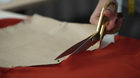 Designer cutting red fabric pattern, workshop for tailoring clothes, design Live Action