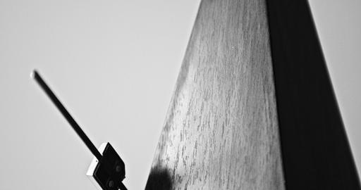 Close-up shot of vintage metronome with pendulum beats slow rhythm on the gray ビデオ