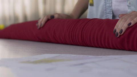 Atelier owner woman rolling out red material fabric on table, textile choice Live Action