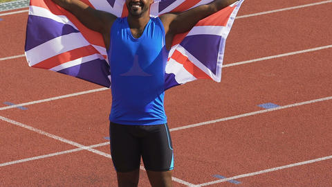 Muscular member of British sports team triumphantly holding flag over his head Live Action