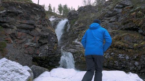 A man traveler stands near a beautiful mountain waterfall and enjoys a beautiful Footage
