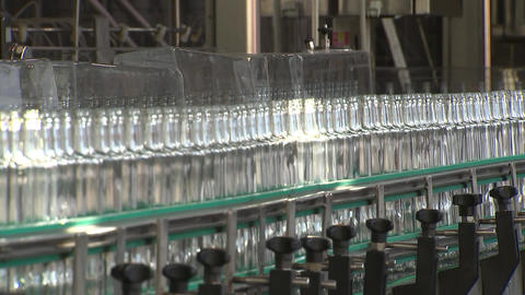 Alcohol factory, glass bottles in a row moving along the conveyor 영상물