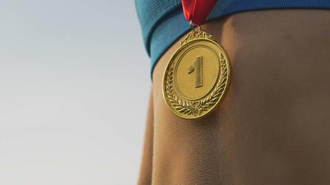 Super closeup shot of gold medal hanging on female athlete's neck, winner Live Action