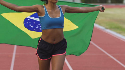 Mixed-race female athlete running on stadium with flag of Brazil, patriotism Live Action