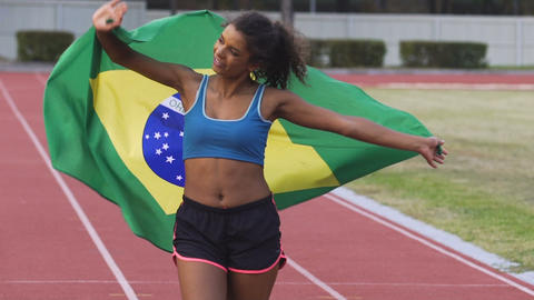 Pretty sportswoman with flag of Brazil radiating joy and celebrating victory Footage