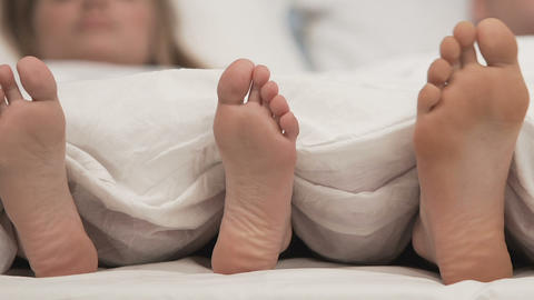 Feet of couple in comfortable bed, honeymoon sleeping time, romantic rest Live Action