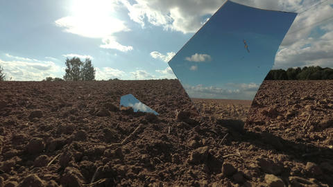 Broken shattered mirror pieces on agriculture field and clouds motion, time lapse Live Action