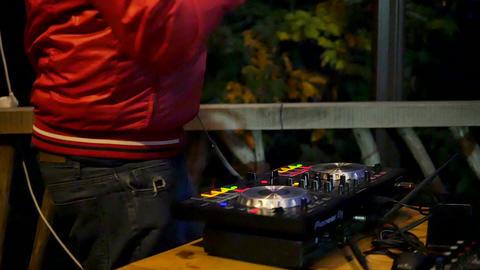 Hands of DJ tweak various mixing tracks controls on dj's deck in the red jacket Live Action