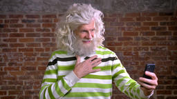 Ridiculous grandfather with white hair and bushy beard waving at web camera on Footage