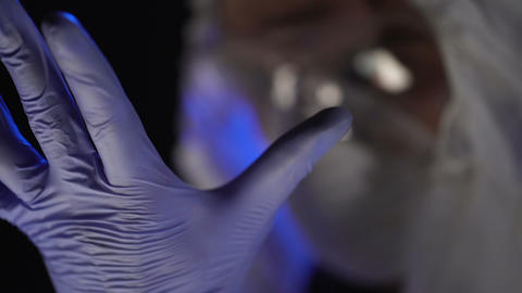 Lab scientist wearing exam gloves, reflection of test tubes in safety glasses Footage