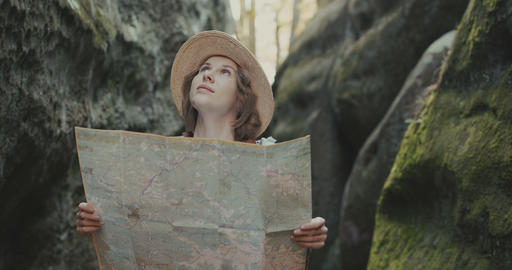 Young happy woman traveling and looking landmarks, girl with map at the rocks Live Action