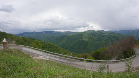 Clouds passing in speed over the high mountains with dense forests on a road tha Footage