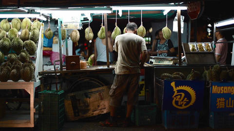 a store owner at his durian stand at night Footage